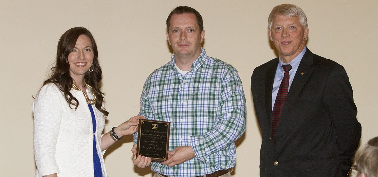 Dr. Julie Estes presents aware to Dr. Glen Borchertand with University President Dr. Tony Waldrop on far right