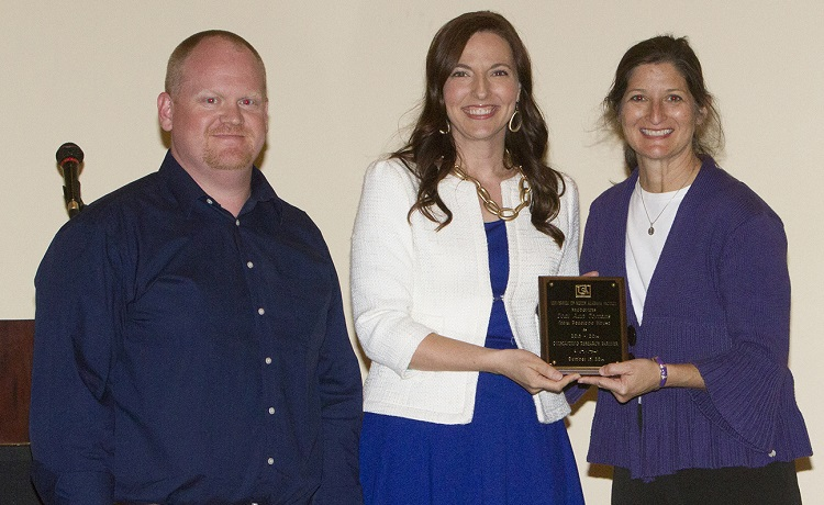 Toni Ann Torrans, director of Penelope House, right, accepts the Outstanding Research Partner Award for 2013-2014. Dr. Phil Smith, left, assistant professor of psychology, nominated Torrans for the award. Also pictured is Dr. Julie Estis, president of the USA Faculty Senate.