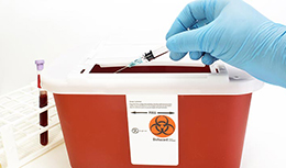 Hand putting needle in biohazard box