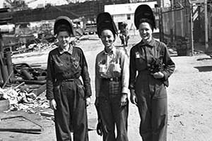 Three women in history smiling wearing work apparel with helmets.