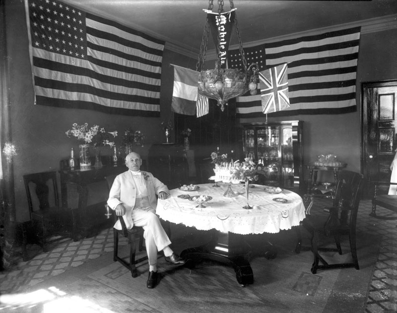 This unidentified man displays a number of flags, among them the Stars and Stripes and the Union Jack.