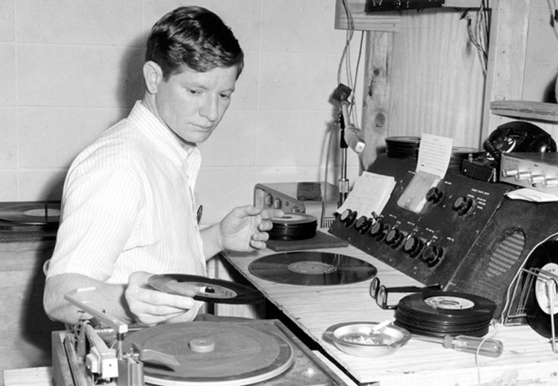 Guy Diehl places a 33 1/3 RPM record on a turntable at the USA student radio station in 1965.
