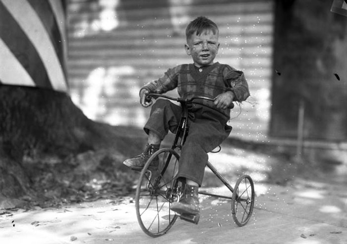 An unidentified boy rides his tricycle, circa 1925.