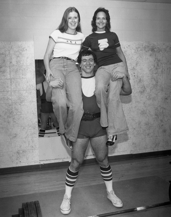 A USA student wrestler hoists two female students on his shoulders.