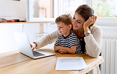 Mother with child in her lap looking at laptop