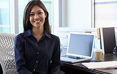 Woman sitting at desk with computer smiling