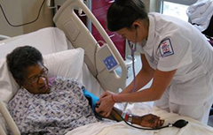 A nurse taking blood pressure of patient