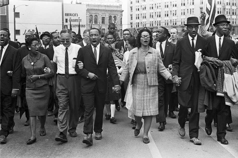 MLK leading the crowd and participants on front row walking arm in arm or hand in hand