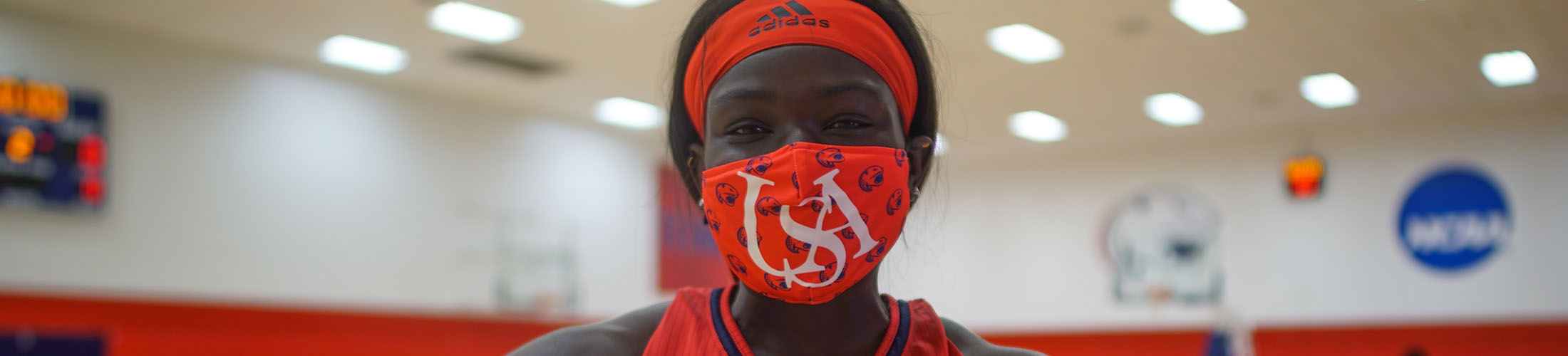 Female athlete on basketball court with mask on.